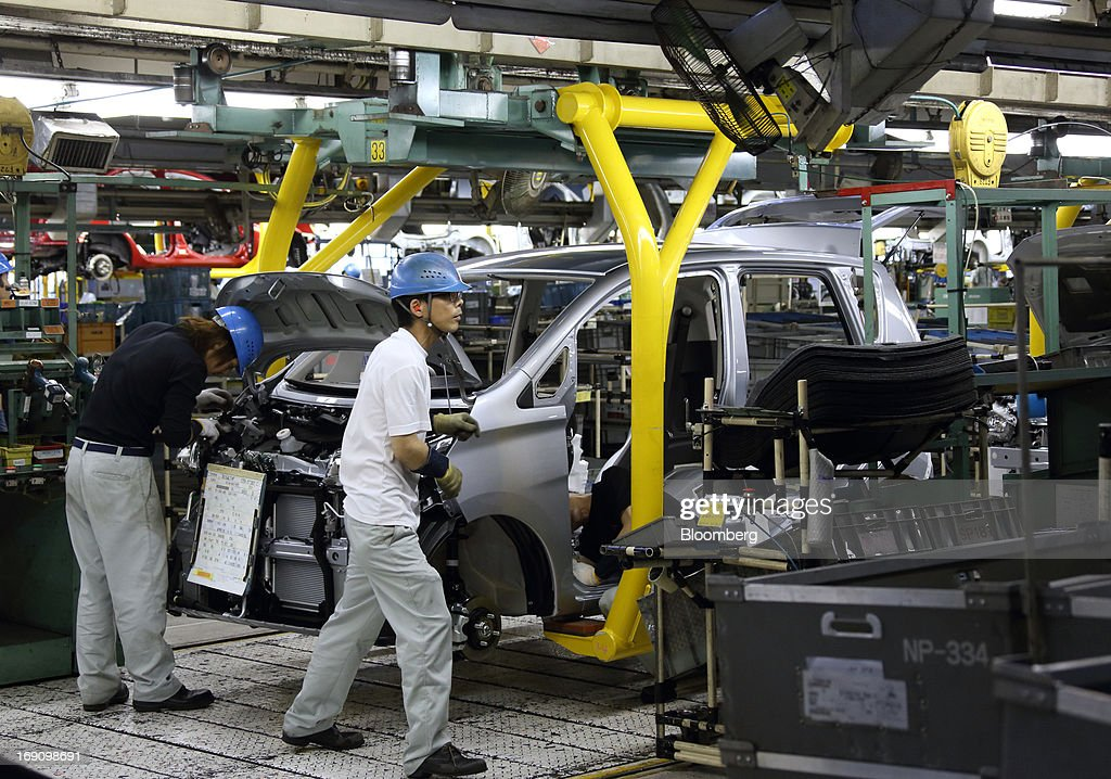 Workers assemble a minicar which will be sold as the Nissan DAYZ by Nissan Motor Co. and Mitsubishi eK Wagon by Mitsubishi Motors Corp. on the production line of the Mitsubishi Motors Mizushima plant in Kurashiki, Okayama Prefecture, Japan, on Monday, May 20, 2013. Nissan will start selling the first minicar it jointly developed with Mitsubishi Motors in Japan next month amid increasing demand from the nation's consumers for smaller and cheaper vehicles. Photographer: Tomohiro Ohsumi/Bloomberg via Getty Images