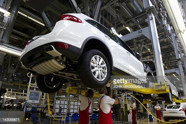 Workers assemble a Porsche Cayenne model on the production line of the German luxury carmaker Porsche plant in Leipzig eastern Germany on March 28...