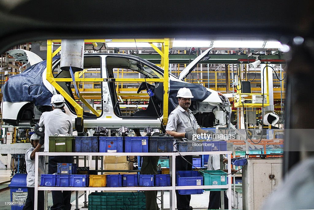 Workers assemble a Tata Motors Ltd. Indigo eCS automobile at the company's factory in Pimpri, Maharashtra, India, on Wednesday, June 19, 2013. Tata Motors announced the introduction of 8 new models on June 19, 2013. Photographer: Dhiraj Singh/Bloomberg via Getty Images