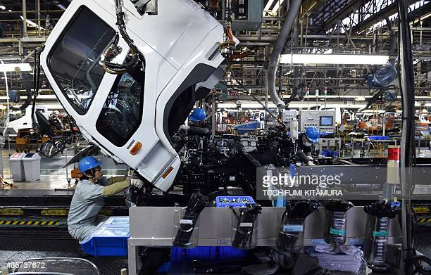 Workers assemble a truck on the line of the Mitsubishi Fuso Truck and Bus Corporation Kawasaki plant in Kawasaki on March 10 2015 The Kawasaki plant...