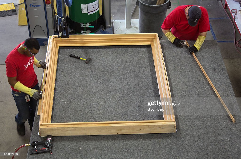 Workers assemble a wood window frame at the Milgard Windows & Doors' manufacturing facility in Tacoma, Washington, U.S., on Wednesday, July 24, 2013. The U.S. Census Bureau is scheduled to release monthly construction spending figures on Aug. 1. Photographer: Tim Rue/Bloomberg via Getty Images