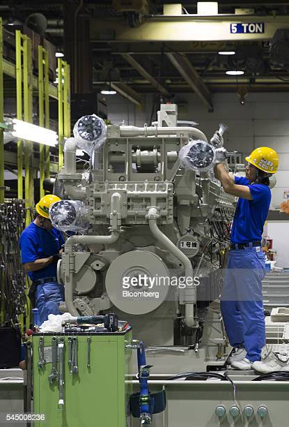 Workers assemble an engine at the Mitsubishi Heavy Industries Engine Turbocharger Ltd plant in Sagamihara Kanagawa Prefecture Japan on Monday July 4...