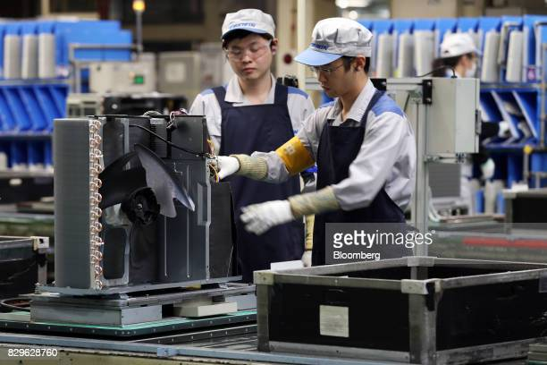 Workers assemble an outdoor unit of a Daikin Industries Ltd split type air conditioner on the production line of the company's Shiga plant in Kusatsu...