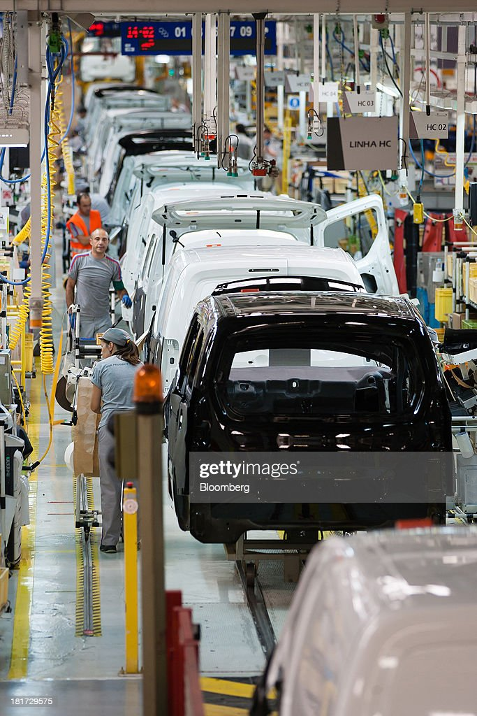 Workers assemble Citroen Berlingo and Peugeot Partner automobiles on the production line at the PSA Peugeot Citroen plant in Mangualde, Portugal, on Monday, Sept. 23, 2013. Some economists point to falling labor costs across southern Europe as a sign the region may be becoming more attractive as a manufacturing base. Photographer: Mario Proenca/Bloomberg via Getty Images