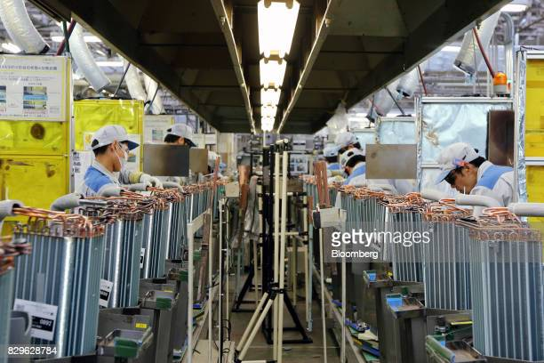 Workers assemble coil condensers for Daikin Industries Ltd air conditioners on the production line of the company's Shiga plant in Kusatsu Shiga...