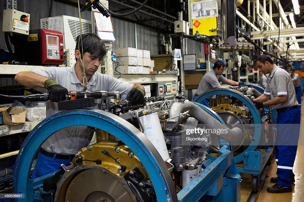 Workers assemble Duratorq diesel motors for Ford Cargo trucks on the engine production line at Ford Otosan, the joint venture between Ford Motor Co.'s Ford Otomotiv Sanayi AS and Koc Holding AS, in Eskisehir, Turkey, on Monday, Nov. 18, 2014. Ford Otomotiv Sanayi AS chief executive officer Haydar Yenigun said in September Turkey is about to 'lose the diamond' which is light commercial vehicle production due to government policies such as tax hikes, ban on their lease, Dunya newspaper says. Photographer: Kerem Uzel/Bloomberg via Getty Images