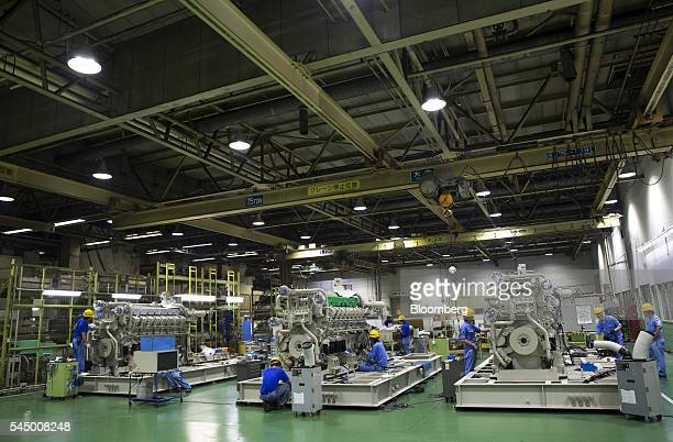 Workers assemble engines at the Mitsubishi Heavy Industries Engine Turbocharger Ltd plant in Sagamihara Kanagawa Prefecture Japan on Monday July 4...