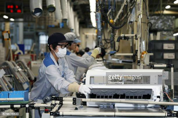Workers assemble indoor units of Daikin Industries Ltd split type air conditioners on the production line of the company's Shiga plant in Kusatsu...