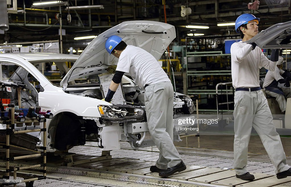 Workers assemble Mitsubishi Motors Corp. vehicles on the production line of the Mitsubishi Motors Mizushima plant in Kurashiki City, Okayama Prefecture, Japan, on Monday, May 20, 2013. Nissan will start selling the first minicar it jointly developed with Mitsubishi Motors in Japan next month amid increasing demand from the nation's consumers for smaller and cheaper vehicles. Photographer: Tomohiro Ohsumi/Bloomberg via Getty Images
