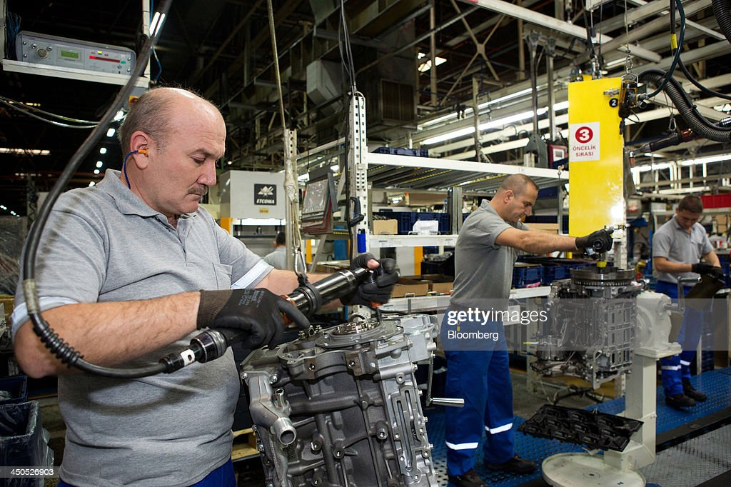 Workers assemble motors for Ford Cargo trucks on the production line at Ford Otosan, the joint venture between Ford Motor Co.'s Ford Otomotiv Sanayi AS and Koc Holding AS, in Eskisehir, Turkey, on Monday, Nov. 18, 2014. Ford Otomotiv Sanayi AS chief executive officer Haydar Yenigun said in September Turkey is about to 'lose the diamond' which is light commercial vehicle production due to government policies such as tax hikes, ban on their lease, Dunya newspaper says. Photographer: Kerem Uzel/Bloomberg via Getty Images