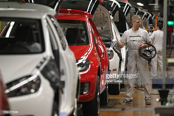 Workers assemble new Volkswagen Golf 6 cars at the Volkswagen factory on February 25 2011 in Wolfsburg Germany Volkswagen and other German carmakers...