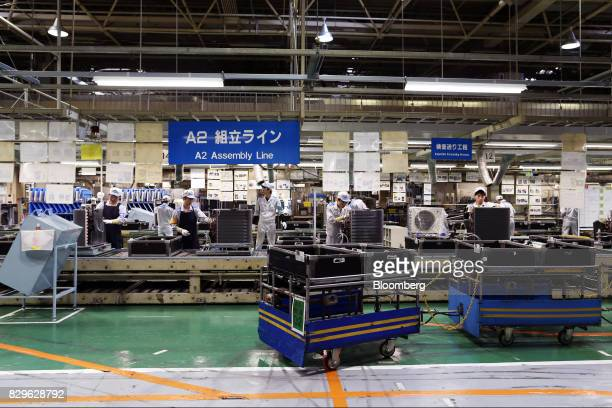 Workers assemble outdoor units of Daikin Industries Ltd split type air conditioners on the production line of the company's Shiga plant in Kusatsu...