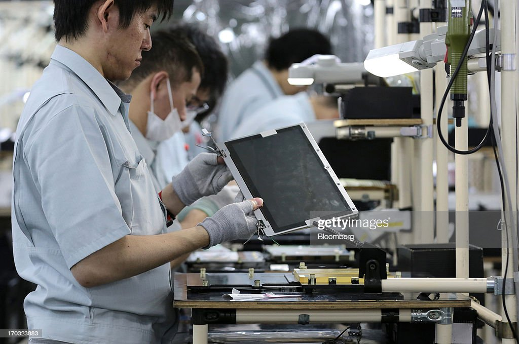 Workers assemble Panasonic Corp.'s laptop computers at the company's plant in Kobe City, Hyogo Prefecture, Japan, on Tuesday, June 11, 2013. Panasonic manufactures electric and electronic products. Photographer: Yuriko Nakao/Bloomberg via Getty Images
