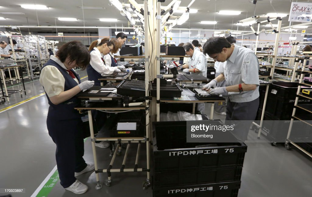 Workers assemble Panasonic Corp.'s Let's Note CF-AX laptop computers on the production line at the company's plant in Kobe City, Hyogo Prefecture, Japan, on Tuesday, June 11, 2013. Panasonic manufactures electric and electronic products. Photographer: Yuriko Nakao/Bloomberg via Getty Images