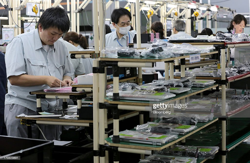 Workers assemble Panasonic Corp.'s Let's Note laptop computers on the production line at the company's plant in Kobe City, Hyogo Prefecture, Japan, on Tuesday, June 11, 2013. Panasonic manufactures electric and electronic products. Photographer: Yuriko Nakao/Bloomberg via Getty Images