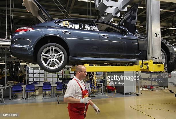 Workers assemble Porsche Cayenne and Panamera cars at an assembly line at the Porsche factory on March 28 2012 in Leipzig Germany The Cayenne and...