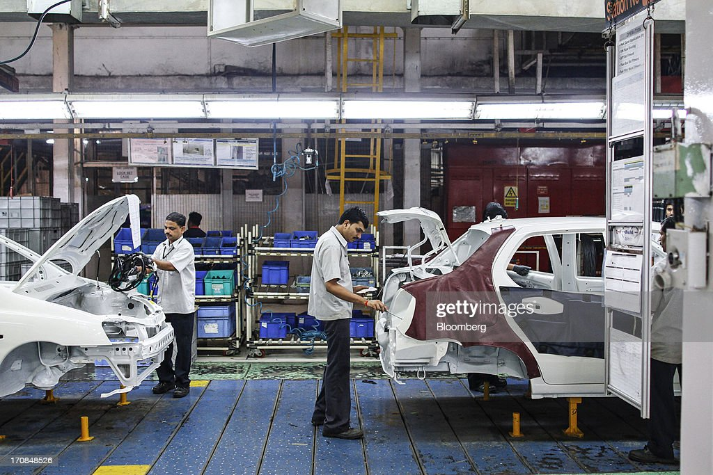 Workers assemble Tata Motors Ltd. Indigo eCS automobiles at the company's factory in Pimpri, Maharashtra, India, on Wednesday, June 19, 2013. Tata Motors announced the introduction of 8 new models today. Photographer: Dhiraj Singh/Bloomberg via Getty Images