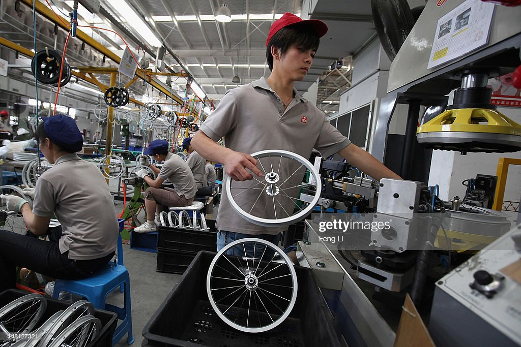 Workers assemble the children's bicycle wheels at the production line of Goodbaby Group Co., Ltd. on July 6, 2012 in Kunshan of Jiangsu Province, China. Chinese Premier Wen Jiabao said Tuesday that stabilizing economic growth is the most pressing matter currently facing China. China's central bank's sudden cut in the benchmark interest rates for the second time in a month confirmed the pessimistic view of the current economic situation.