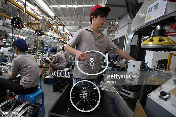 Workers assemble the children's bicycle wheels at the production line of Goodbaby Group Co Ltd on July 6 2012 in Kunshan of Jiangsu Province China...