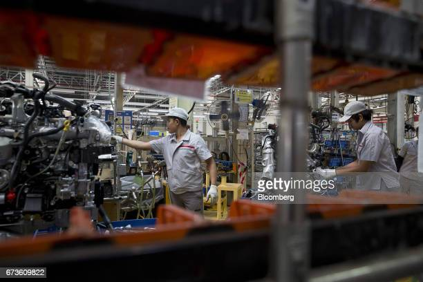 Workers assemble the engines of Nissan Motor Co Navara pickup truck engines at the company's plant in Samut Prakan Thailand on Tuesday April 25 2017...