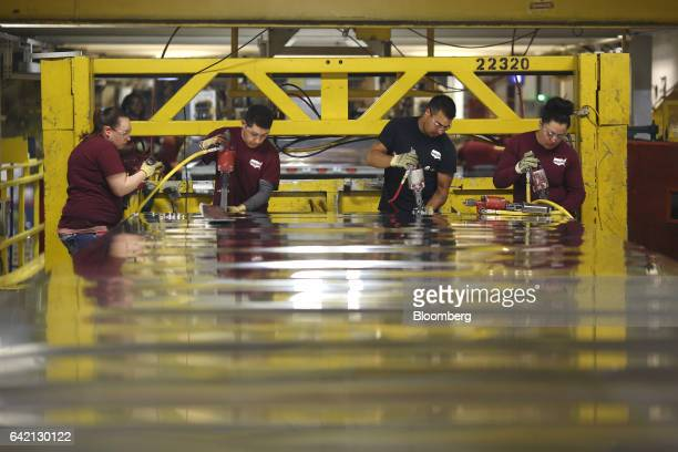 Workers assemble the roof for a semi trailer on the factory floor at the Wabash National Corp manufacturing facility in Lafayette Indiana US on...