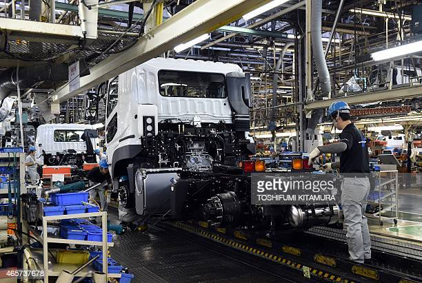 Workers assemble trucks on the line of the Mitsubishi Fuso Truck and Bus Corporation Kawasaki plant in Kawasaki on March 10 2015 The Kawasaki plant...