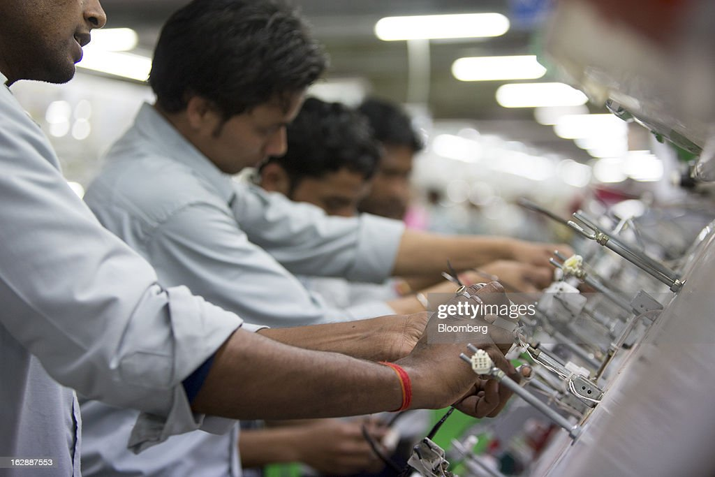 Workers assemble wire harnesses at the Motherson Sumi Systems Ltd. wiring harness plant in Faridabad, India, on Thursday, Feb. 28, 2013. Motherson Sumi Systems Ltd., 25 percent owned by Sumitomo Electric Industries Ltd. and India's biggest auto parts maker, supplies rear view mirrors, bumpers and body panels to clients including Porsche Automobil Holding SE, Bayerische Motoren Werke AG and Volkswagen AG. Photographer: Brent Lewin/Bloomberg via Getty Images