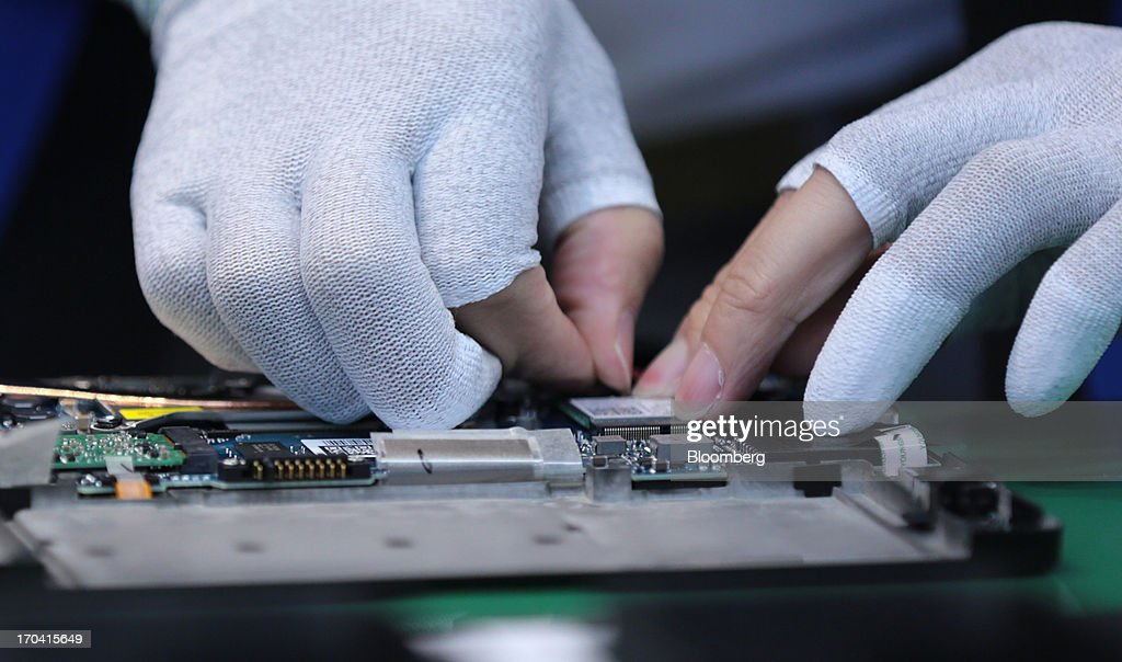 A workers assembles components of Panasonic Corp.'s Let's Note CF-AX3 laptop computer during a demonstration at the company's plant in Kobe City, Hyogo Prefecture, Japan, on Tuesday, June 11, 2013. Panasonic manufactures electric and electronic products. Photographer: Yuriko Nakao/Bloomberg via Getty Images