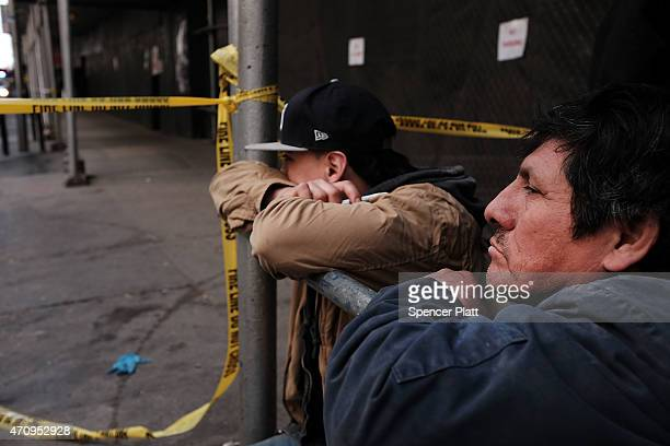 Workers at a construction site where a worker was killed this afternoon in a crane accident look out at the scene on April 24 2015 in New York City...