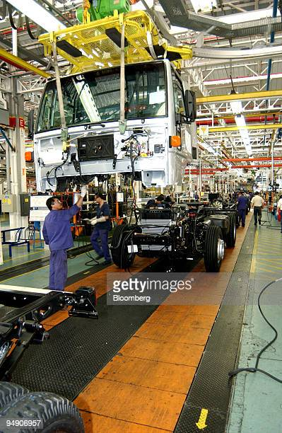 Workers at a Ford plant in Sao Bernardo do Campo near Sao Paulo city in Brazil prepare to attach a cab to its chaise on the assembly line July 2 2004
