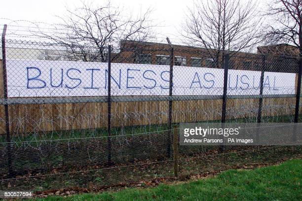 Workers at Huntingdon Life Sciences the drug testing laboratory targeted by animal activists place a banner on the fences outside their offices in...