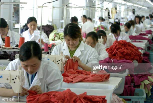 Workers at the Ningbo Silk Trend garment factory go about their chores in the eastern Chinese port city of Ningbo 28 April 2005 Hundreds of sewing...