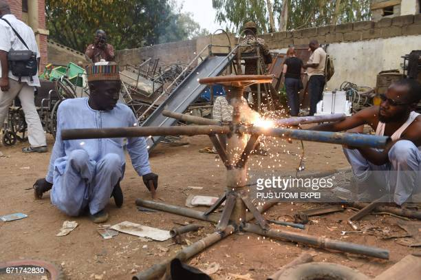 Workers at the Polio Victims Trust Association try to weld a panel at the workshop in Kano northwest Nigeria on April 21 2017 The World Health...