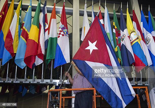 Workers at the US Department of State add the Cuban flag at to the display of flags inside the main entrance at 202 'C' Street at 4am local time in...