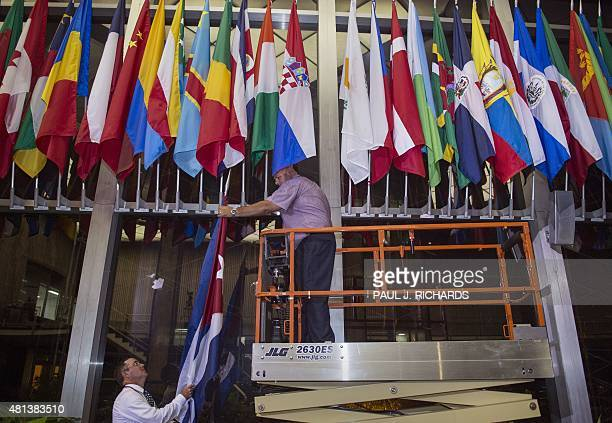 Workers at the US Department of State add the Cuban Flag at to the display of flags inside the main entrance at 202 'C' St 400 am EDT July 20 2015 in...
