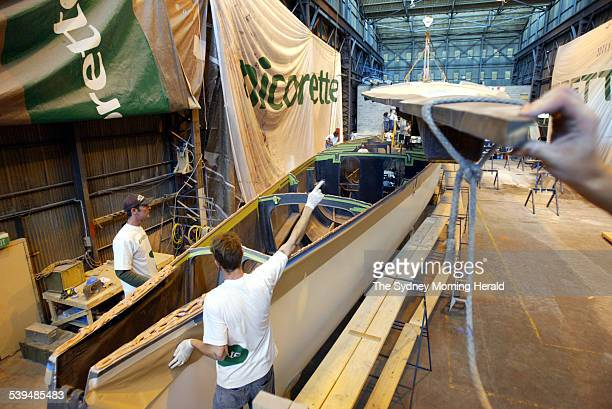 Workers at the Woolwich Dock position the deck of the old Nicorette racing yacht as it is lowered over a new carbon fibre hull on 7 October 2004 The...