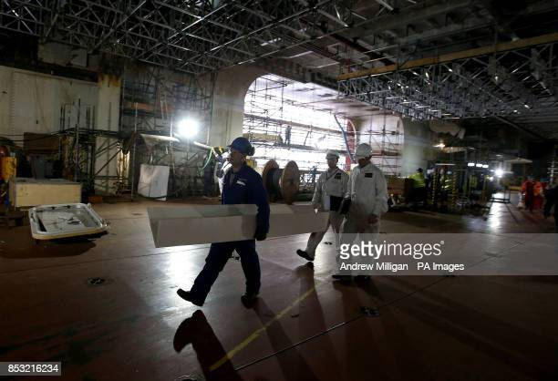 Workers at work in the hanger of HMS Queen Elizabeth Aircraft Carrier at Rosyth Docks
