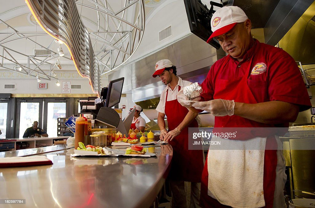 Workers at Z-Burger in Washington, DC, prepare food during the lunch hour rush October 1, 2013. The fast-food chain is promising free hamburgers to federal workers who find themselves furloughed after the US government shutsdown Tuesday, its founder and proprietor Peter Tabibian said. AFP PHOTO/Jim WATSON