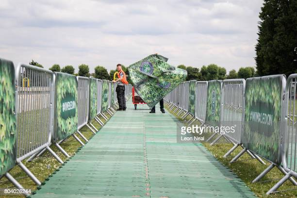 Workers attach branded signs to barriers near the concrete bollards and security gates in the public queueing zone outside the All England Tennis...