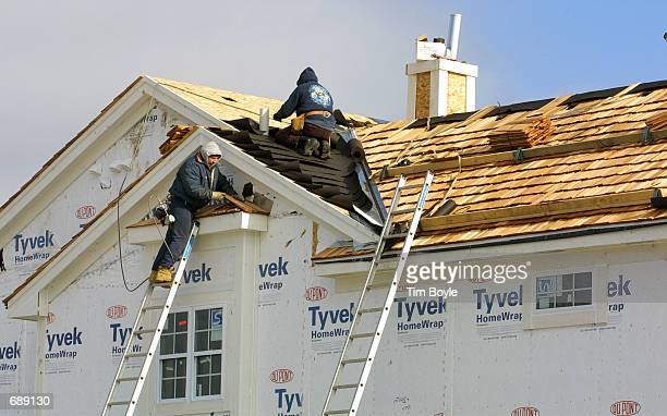 Workers attach cedar shingles to a roof of a new singlefamily home under construction December 27 2001 in Glenview IL The Commerce Department...