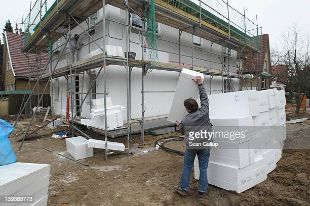 Workers attach styrofoam blocks as insulation to the exterior of a new house under construction on February 18 2012 in Berlin Germany The German...