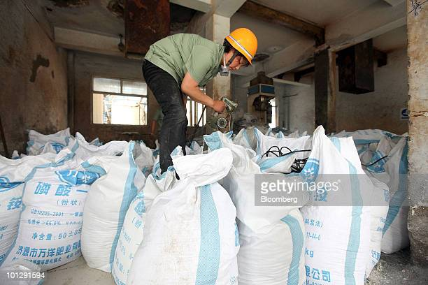 Workers bag sulfphur a chemical byproduct produced while making fertilizer at the China XLX Fertiliser Ltd plant in Xinxiang Henan province China on...