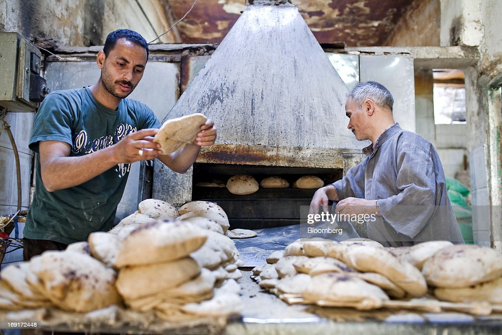 Workers bake bread in an oven inside a bakery in Cairo, Egypt, on Monday, May 20, 2013. Egypt will curb wheat imports by 31 percent to 8 million metric tons in 2012-13, still enough to make it the world's biggest buyer, the U.S. Department of Agriculture estimates. Photographer: Shawn Baldwin/Bloomberg via Getty Images