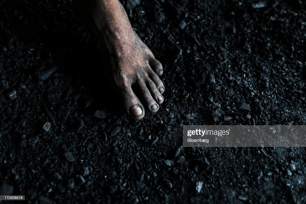 A worker's bare foot stands on the coal covered ground of a coal wholesale market in Mumbai, India, on Tuesday, July 2, 2013. India, the worlds third-largest coal consumer, imported 43 percent more of the fuel than a year ago on increased demand from power stations and steelmakers, according to shipping data, and is set to eclipse China as the top importer of power station coal by 2014. Photographer: Dhiraj Singh/Bloomberg via Getty Images