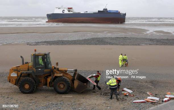 Workers begin to clear the beach of debris from the cargo ship Riverdance which has run aground at Blackpool due to the high winds