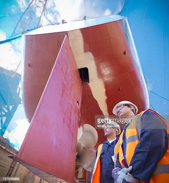 Workers below underside of ship in dry dock