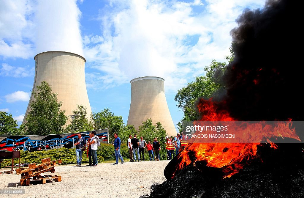 Workers block the access to the nuclear power plant of Nogent-sur-Seine on May 26, 2016, during a protest against controversial labour market reforms that has already severely disrupted fuel supplies. With two weeks until France hosts the Euro 2016 football championships, the country has been paralysed by a series of transport strikes and fuel shortages that has heaped pressure on the deeply unpopular Socialist government. / AFP / FRANCOIS