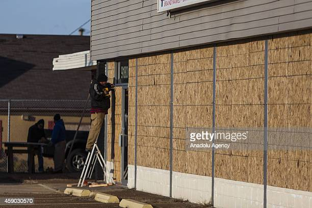 Workers board up the windows of Furniture Mattresses For Less on West Florissant Ave in preparation for possible protests after the Grand Jury...
