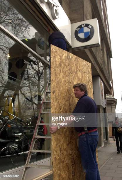 Workers board up the windows of the BMW car dealership in Park Lane London ahead of the May Day demonstrations against capitalism Police leave has...