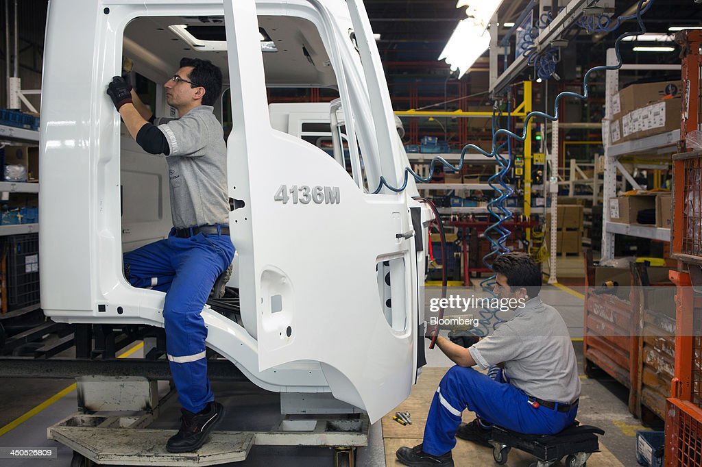 Workers bolt parts to a Ford Cargo truck drivers cabin section on the production line at Ford Otosan, the joint venture between Ford Motor Co.'s Ford Otomotiv Sanayi AS and Koc Holding AS, in Eskisehir, Turkey, on Monday, Nov. 18, 2014. Ford Otomotiv Sanayi AS chief executive officer Haydar Yenigun said in September Turkey is about to 'lose the diamond' which is light commercial vehicle production due to government policies such as tax hikes, ban on their lease, Dunya newspaper says. Photographer: Kerem Uzel/Bloomberg via Getty Images